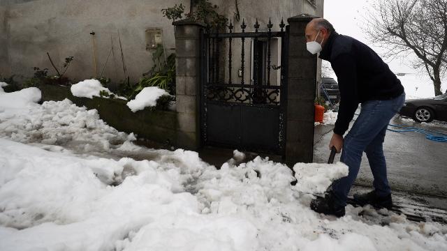 Alfonso Arias, limpiando la entrada de su casa. VICTORIA RODRÍGUEZ